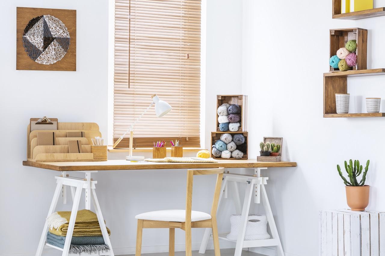DIY yarn art on a white wall of a scandinavian crafts room inter